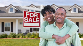 Happy African American Couple In Front of Beautiful House and Fo. R Sale Real Estate Sign Stock Image