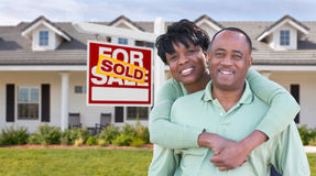 Happy African American Couple In Front of Beautiful House and So. Ld For Sale Real Estate Sign Stock Photo
