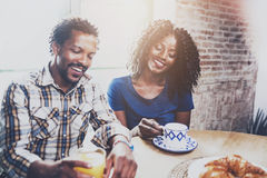 Happy african american couple are having breakfast together in the morning at wooden table.Smiling black man and his Stock Photo