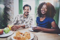 Happy african american couple are having breakfast together in the morning at the wooden table.Smiling black man and his Royalty Free Stock Photo