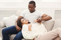 Smiling black couple having rest on sofa at home. Happy african-american couple having rest at cozy home. Family leisure, lazy weekend and relaxation concept Royalty Free Stock Photos
