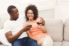 Smiling black couple drinking wine on sofa at home. Happy african-american couple having rest at cozy home, laughing and drinking wine. Family leisure, lazy Royalty Free Stock Image