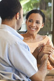 Happy African American Couple Holding Hands. A happy African American man and woman couple sitting down and holding hands Royalty Free Stock Image