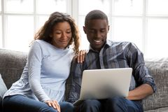 Happy African American couple in love using laptop together stock photos
