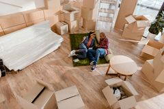Happy african american couple in new apartment. With cardboard boxes stock photography