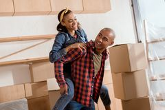 happy african american couple piggybacking in new apartment stock images