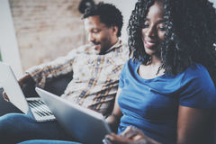 Happy african american couple relaxing together on the couch.Young black man and his girlfriend using laptop at home in Royalty Free Stock Image