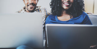 Happy african american couple relaxing together on the couch.Young black man and his girlfriend using laptop at home in Stock Image