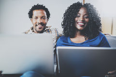 Happy african american couple relaxing together on the sofa.Young black man and girl using modern notebooks at home in Stock Photography