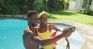 Happy african american couple standing in swimming pool taking selfie and smiling in sunny garden