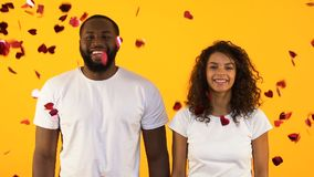 Happy African-American couple standing under heart-shaped confetti, relationship stock video