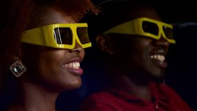Happy African American couple watching movie 3D In. Theatre. Close up. looking at the screen and smiling stock video