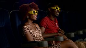 Happy African American couple watching movie 3D In. Happy African American couple watching movie. wearing glasses 3D In theatre. Close up. looking at the screen stock video