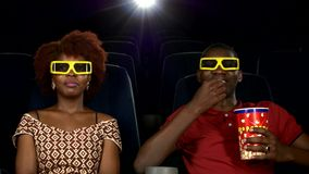 Happy African American couple, watching movie In. Theatre, Close up. smiles, laughter, glances at each other. big package of popcorn in his hands stock footage