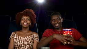 Happy African American couple, watching movie In. Theatre, Close up. smiles, laughter, glances at each other. big package of popcorn in his hands stock video