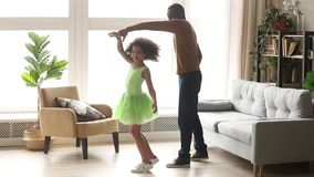 Happy african dad dancing with child daughter in living room
