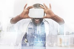 Happy African American doctor wearing virtual glasses. Incredible emotions. Close up of pleasant African American doctor wearing virtual glasses and touching Stock Photo