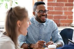 Diverse colleagues have fun laughing during casual office meetin. Happy African American employee have fun at casual meeting in office, excited black male worker royalty free stock photography