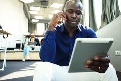 Happy african american entrepreneur using tablet computer. Happy african american entrepreneur using tablet computer royalty free stock photo