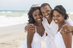 Happy African American Family On Beach. A happy smiling laughing African American family of father mother & daughter at the beach in the summer Stock Photo