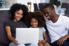 Happy african family with child having fun using laptop together royalty free stock photography