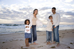 Happy African-American family of four on beach. Happy African-American family with two children hugging on beach Royalty Free Stock Photos