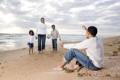 Happy African-American family of four on beach. Father waiting with open arms Stock Images