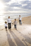 Happy African-American family of four on beach. Happy African-American family of four standing on beach with beautiful sunlight Stock Image