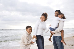 Happy African-American family of four on beach. Happy African-American family with two children on beach Stock Photo