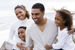 Happy African-American family of four on beach stock photography