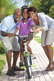 Happy African American Family & Girl Riding Bike. A young African American family with girl child riding her bicycle and her happy excited parents giving Royalty Free Stock Photos