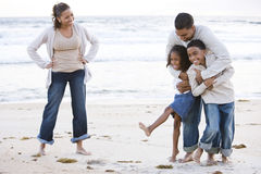 Happy African-American family laughing on beach. Happy African-American family with two children laughing together on beach Stock Photo