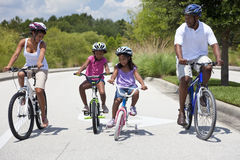 Happy African American Family Riding Bikes. A Black African American family of two parents and two children, two girls, cycling together royalty free stock image