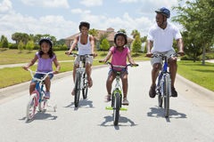 Happy African American Family Riding Bikes. A Black African American family of two parents and two children, two girls, cycling together Royalty Free Stock Photography