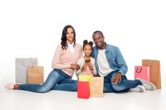 happy african american family with shopping bags and credit card smiling at camera stock photography