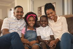 Happy African American family sitting on the sofa and looking at camera royalty free stock image