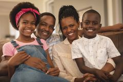 Happy African American family sitting on the sofa and looking at camera royalty free stock photos