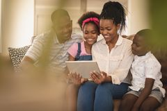 Happy African American family sitting on the sofa and using digital tablet stock image