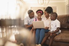 Happy African American family sitting on the sofa and using laptop royalty free stock photos