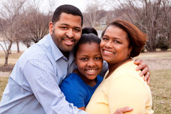 Happy African American Family Smiling Outside. African American mother and father with their daughter Stock Photos