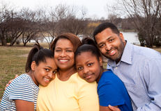 Happy African American Family Smiling Outside. African American mother and father with their two daughters Royalty Free Stock Photography