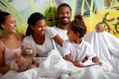 Happy African American family spending time together with tablet stock image
