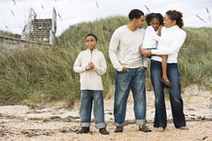 Happy African-American family standing together. Happy African-American family with two children standing together on beach Royalty Free Stock Photography