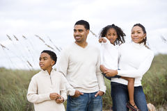 Happy African-American family standing together. Happy African-American family with two children standing together at beach by sand dunes and sea oats grass Royalty Free Stock Image