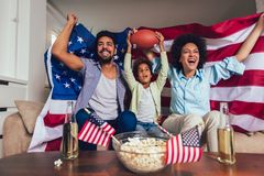 African American family of three watching tv and cheering sport games on sofa at home royalty free stock images