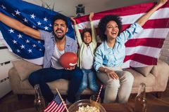 African American family of three watching tv and cheering sport games on sofa at home. Happy African American family of three watching tv and cheering sport royalty free stock image