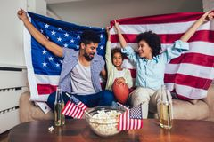 African American family of three watching tv and cheering sport games on sofa at home. Happy African American family of three watching tv and cheering sport stock images