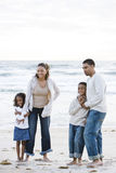 Happy African-American family together on beach. Happy African-American family with two children standing together on beach Stock Image