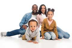 Happy african american family with two kids sitting together and smiling at camera. On white royalty free stock image