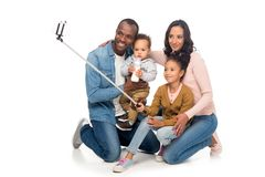 Happy african american family with two kids taking selfie with smartphone. Isolated on white stock photos